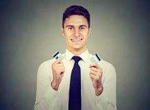 El hombre joven libre de la deuda feliz que sostenía una tarjeta de crédito cortó en dos pedazos imágenes de archivo libres de regalías