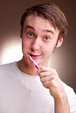 El hombre joven limpia los dientes Foto de archivo