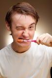 El hombre joven limpia los dientes Foto de archivo libre de regalías