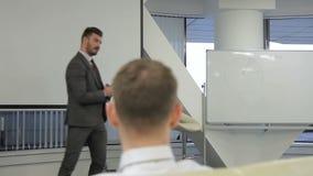 El hombre joven lleva a cabo el seminario para los empleados en compañía principal almacen de metraje de vídeo