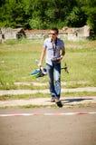 El hombre joven lleva el helicóptero modelo después de su demostración en competencias aficionadas fotos de archivo libres de regalías