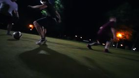 El hombre joven lleva la bola en un campo verde, otros jugadores está intentando llevarse su bola
