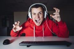 El hombre joven loco juega a un juego en casa en su ordenador Videojugador emocional enojado porque lo mataron en juego de ordena Imagen de archivo