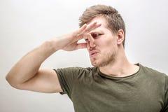 El hombre joven mantiene la nariz cerrada Él huele el mún olor Aislado en el fondo blanco imagenes de archivo