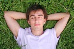 El hombre joven miente en la pista de la hierba en ojos cerrados las manos Fotografía de archivo