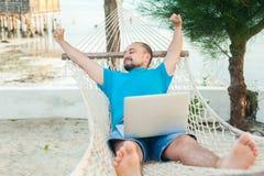 El hombre joven miente en una hamaca y es feliz con un t acertado imagen de archivo libre de regalías