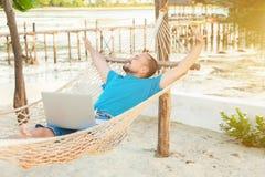 El hombre joven miente en una hamaca y es feliz con un t acertado imagen de archivo