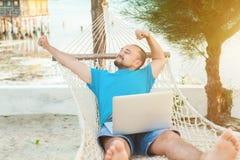 El hombre joven miente en una hamaca y es feliz con un t acertado fotos de archivo