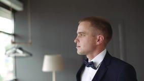 El hombre joven mira cuidadosamente hacia fuera la ventana Hombre de negocios en traje de negocios azul almacen de metraje de vídeo