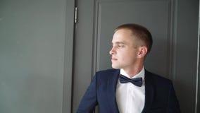 El hombre joven mira cuidadosamente hacia fuera la ventana El hombre de negocios en un traje de negocios azul se inclinó contra l metrajes