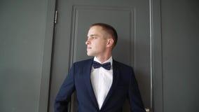 El hombre joven mira cuidadosamente hacia fuera la ventana Un hombre de negocios en un traje de negocios azul que se inclina cont almacen de metraje de vídeo