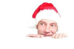 El hombre joven mira en un sombrero de la Navidad Imagenes de archivo