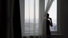 El hombre joven mira hacia fuera la ventana la ciudad y bebe té almacen de metraje de vídeo