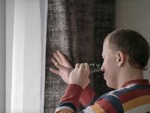 El hombre joven mira hacia fuera la ventana con los prismáticos foto de archivo