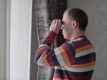 El hombre joven mira hacia fuera la ventana a través de los prismáticos foto de archivo