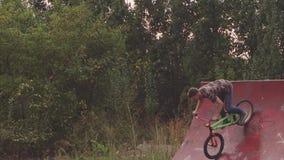 El hombre joven monta una bici de BMX en el parque, él realiza un truco llamado Nouhend metrajes