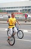 El hombre joven monta una bici que mira la cámara Fotografía de archivo libre de regalías