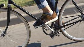 El hombre joven monta una bicicleta a lo largo de la calle almacen de video