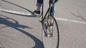 El hombre joven monta una bicicleta a lo largo de la calle almacen de metraje de vídeo