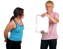 El hombre joven muestra los psges en blanco para la muchacha. Imagen de archivo