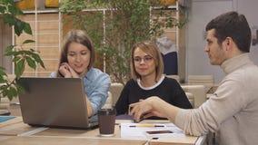 El hombre joven muestra a sus compañeros de trabajo algo en el ordenador portátil en el eje de trabajo
