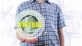 El hombre joven muestra un holograma de la tierra y del texto del planeta virtuales metrajes