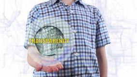 El hombre joven muestra un holograma de la transparencia de la tierra y de texto del planeta almacen de video
