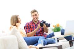 El hombre joven muestra una foto de su novia que se sienta en la sala de estar Fotos de archivo libres de regalías