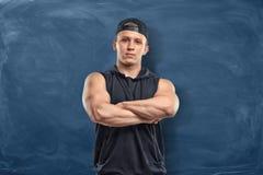 El hombre joven muscular en la ropa de deportes que se colocaba con sus brazos dobló en el fondo azul marino Fotografía de archivo libre de regalías