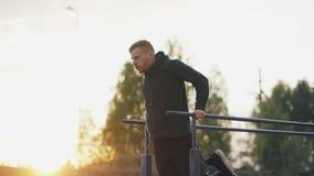 El hombre joven muscular hermoso tiene entrenamiento del entrenamiento en el parque en puesta del sol metrajes