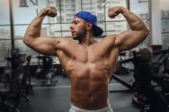 El hombre joven muscular muestra sus músculos en el gimnasio Imágenes de archivo libres de regalías