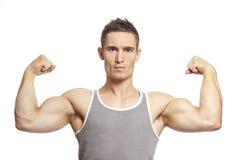 El hombre joven muscular que dobla el brazo muscles en equipo de los deportes imagenes de archivo