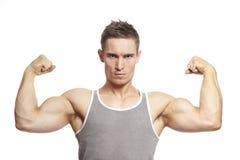 El hombre joven muscular que dobla el brazo muscles en equipo de los deportes imagen de archivo