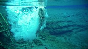 El hombre joven muscular se zambulle en el lago azul claro