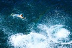 El hombre joven nada en el mar Imagen de archivo