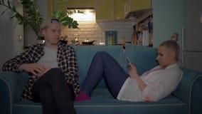 El hombre joven no es feliz que su novia utiliza el teléfono durante su tiempo junta Un hombre joven y un amigo se sientan almacen de video