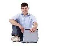 El hombre joven, ocasional que se sienta en suelo abre la computadora portátil Fotos de archivo libres de regalías