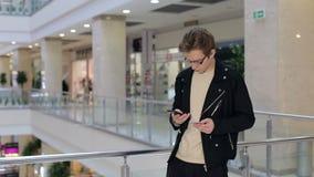 El hombre joven paga compras por la tarjeta de crédito usando el teléfono en una alameda metrajes