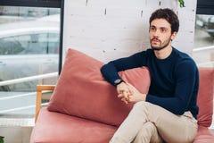 El hombre joven pensativo hermoso de la moda está esperando alguien imagen de archivo libre de regalías