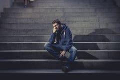 El hombre joven perdió en la depresión que se sentaba en las escaleras de tierra del hormigón de la calle Fotos de archivo libres de regalías