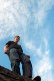 El hombre joven permanece en el borde de piedra Foto de archivo libre de regalías