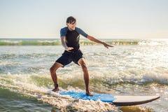 El hombre joven, persona que practica surf del principiante aprende practicar surf en una espuma del mar en el B foto de archivo