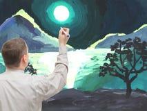 El hombre joven pinta una imagen Fotografía de archivo libre de regalías