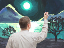 El hombre joven pinta una imagen Imagen de archivo