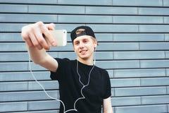 El hombre joven positivo en un casquillo y una camiseta negra hace el selfie y escuchar la música en la pared del fondo Fotografía de archivo