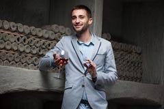 El hombre joven prueba el vino rojo Foto de archivo
