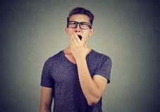 El hombre joven que bosteza con entrega su boca imágenes de archivo libres de regalías