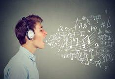 El hombre joven que canta con música observa la salida de la boca Imagen de archivo libre de regalías