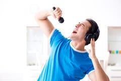 El hombre joven que canta en casa Karaoke Foto de archivo