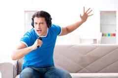 El hombre joven que canta en casa Karaoke Imágenes de archivo libres de regalías